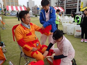 """県民広場の「体験コーナー」では本校の1年生が""""お年寄り体験スーツ""""のお手伝い"""